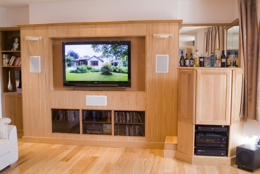 Solid oak living room and home cinema with steps up to fully equipped bar. Integrated storage units below for AV units and sub woofer.